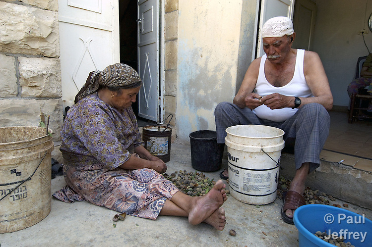A man and woman shell almonds in the West Bank village of Aboud.