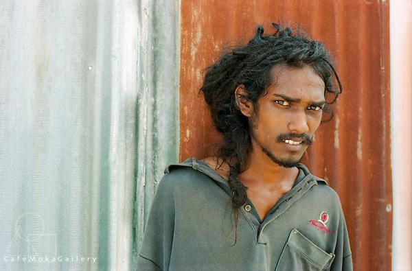 Street portrait of wild looking young male Dougla with dreadlocks and piercing gaze