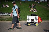 Berlin, Männer ziehen am Donnerstag (09.05.13) im Mauer Park in Berlin einen Wagen der Musik abspielt. Foto: Timur Emek/CommonLens
