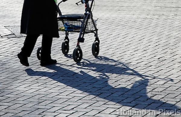 Vrouw loopt met rollator op straat