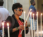 VMI Vincentian Heritage Tour: Georgianna Torres Reyes lights a candle inside the Saint-Philibert de Tournus church, a former Benedictine abbey. Members of the VMI toured the site  Wednesday, June 29, 2016, as they visited the town of Tournus in southern France. (DePaul University/Jamie Moncrief)