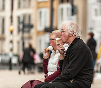 UK Weather: Aberystwyth, Ceredigion, West Wales. A couple enjoy an icecream at the promenade as people are out in force today taking full advantage of the summer heat, with temperatures of 23 in town. With temperatures reportedly hitting 25 in other parts of the United Kingdom.