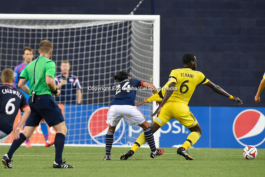 July 26, 2014 - Foxborough, Massachusetts, U.S. - New England Revolution midfielder Lee Nguyen (24) holds onto Columbus Crew midfielder Tony Tchani's (6) jersey during the MLS game between the Columbus Crew and the New England Revolution held at Gillette Stadium in Foxborough Massachusetts.  Eric Canha/CSM