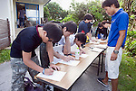 ANA InterContinental Manza Beach Resort staff helping with the the Team Tyura Sango coral restoration project assist volunteers with signing up for the coral planting expedition outside the hotel dive shop  in Onna Village, Okinawa Prefecture, Japan, on Saturday, June 23, 2012. Photographer: Robert Gilhooly