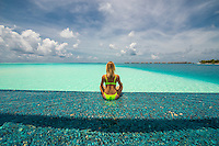 Maldives, Rangali Island. Conrad Hilton Resort. Woman in infinity pool near the ocean. (MR)