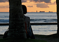 A young woman contemplates life as the sun sets over Waikiki Beach