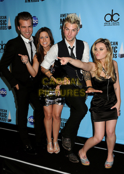 GLORIANA - Tom Gossin, Cheyenne Kimball, Mike Gossin and Rachel Reinert .At the 2009 American Music Awards - Press Room held at the Nokia Theatre L.A. Live, Los Angeles, California, USA, .22nd November 2009..AMA AMAs full length band group black waistcoat tie suit white shirt strapless sequined sequin dress silver sandals strappy tattoos hand finger pointing trophy award .CAP/ADM/BP.©Byron Purvis/AdMedia/Capital Pictures.