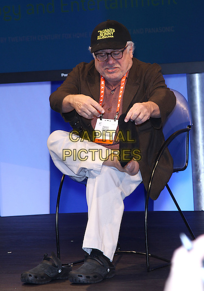 Danny Devito.Danny Devito makes an appearance at the Panasonic booth at the 2013 Consumer Electronics Show at the Las Vegas Convention Center, Las Vegas, NV., USA..January 9th, 2013.full length brown jacket baseball cap hat beige trousers chair sitting leg glasses foot up taking off removing shoes socks feet funny .CAP/ADM/MJT.© MJT/AdMedia/Capital Pictures.