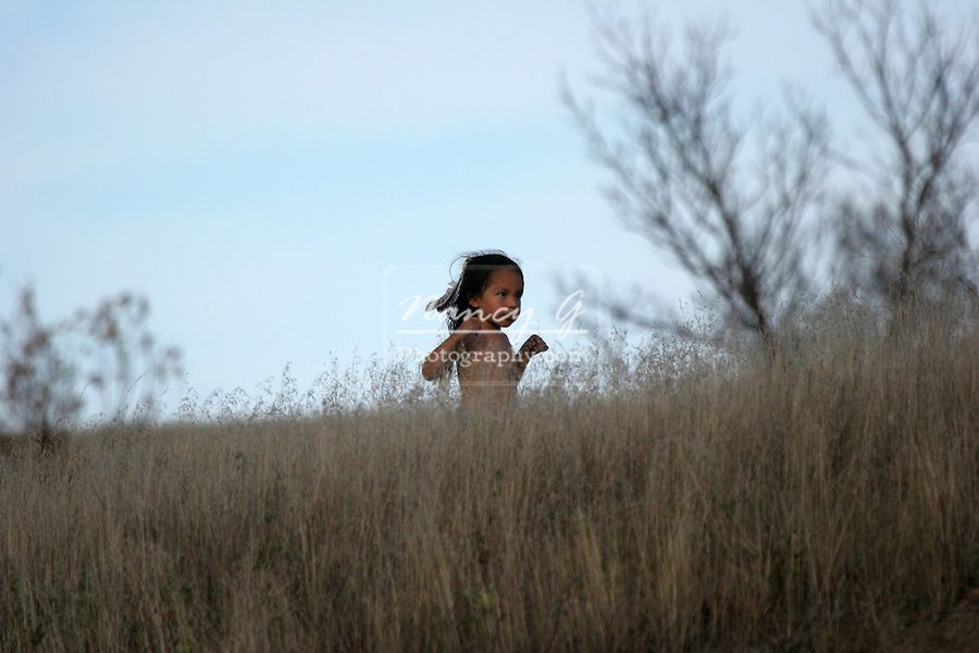 A Native American Indian boy running in the dried grasses