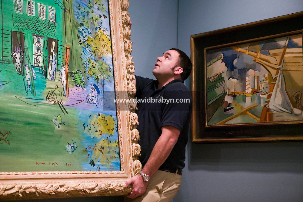 28 April 2006 - New York City, NY - An employee hangs Raoul Duffy's painting, Nogent-sur-Marne, at the Sotheby's auction house in New York City, USA, 28 April 2006. The piece, part of a major sale of impressionist and modern art, is expected to bring in between $500,000 and $700,000.