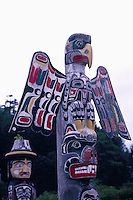 Kwakwaka'wakw (Kwakiutl) Memorial Totem Poles, on Namgis Burial Grounds, Alert Bay, Cormorant Island, BC, British Columbia, Canada - Thunderbird sits atop Grizzly Bear in foreground