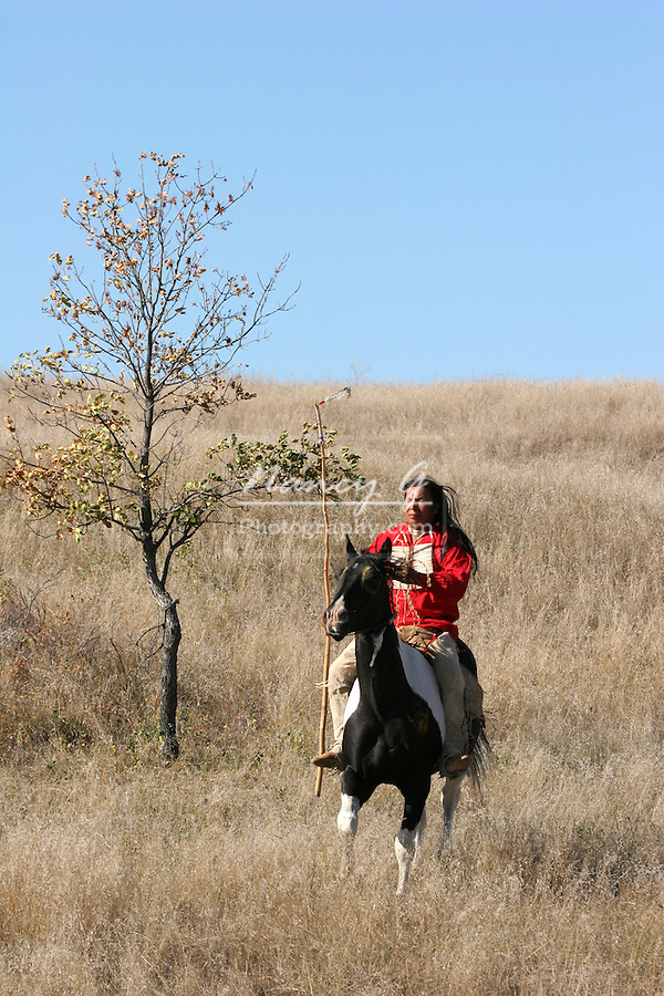 A Native American Indian man riding horseback on an Indian horse on the prairie of South Dakota