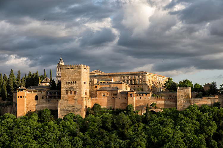 Last lights of day under a brooding sky, dramatizes the hill-top Alhambra in Granada.