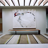 A bespoke bench by Shamir Shah sits beneth a large painting by Weston Teruya while the striped rug echoes the lines of the beams