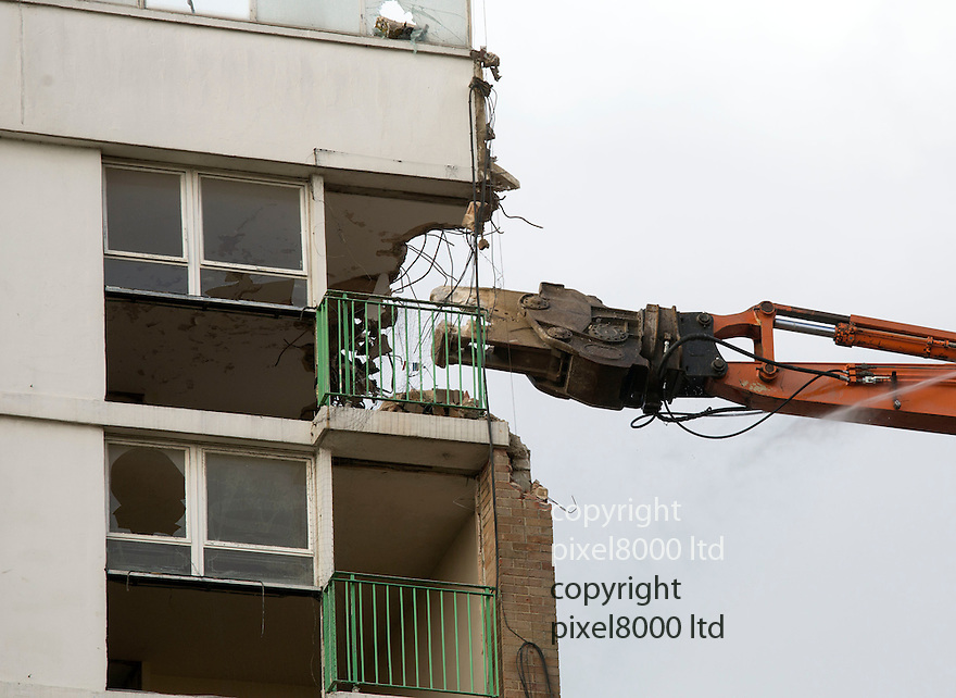Pic shows: Roman House, Mardyke Estate, Dagenham East London - Demolition of last of famous tower blocks as used in Made In Dagenham film and Fish Tank.<br /> <br /> One of the first things demolished was the CCTV camera on top of the block<br /> <br /> Residents came out in force to see <br /> <br /> originally used to house Ford Motor Company workers.<br /> <br /> An &pound;80m regeneration project which is transforming an infamous London housing estate into a thriving community today reached a major milestone when the demolition of the last remaining tower block got underway. <br />  <br /> Residents came together to celebrate as a monster muncher started to bring down the final 12 storey tower block, marking a historic moment for the Rainham estate, which achieved notoriety in recent years having appeared in the films Made in Dagenham and Fish Tank.<br />  <br /> Orchard Village &ndash; previously known as the Mardyke Estate&ndash; was a 1960s high rise estate that over time became dilapidated and a haunt for anti social behaviour. The estate&rsquo;s reputation for crime meant that no one on the housing list of over 4,000 wanted to live there, resulting in flats remaining empty. <br /> <br /> <br /> <br /> <br /> Pic by Gavin Rodgers/Pixel 8000 Ltd