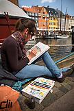DENMARK, Copenhagen, Street Painter paints in the Nyhavn district, Europe