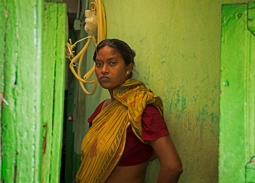 A women at the entrance of a colourful building. Life in the streets of Kolkata, West Bengal, India