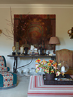 In the living room, carefully selected collection of items is arranged on a wrought-iron console table; plaster casts of feet stand in a row beneath the table and an artwork with an image of a coat of arms hangs on the wall behind. A Napoleon III slipper chair is covered in vintage wool felt with panels of an embroidered suzani by Robert Kime, the ottoman is slipcovered in a custom-stripe linen by Twill Textiles
