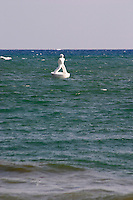 A white sculpture of a man floating like a buoy in the sea. Sitges, Catalonia, Spain