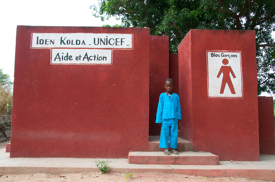 UNICEF/Senegal/Shryock/2009.A young boy in the village of Boguel in Southern Senegal stands next to a new bathroom installed as part of the Essential Learning Package program.