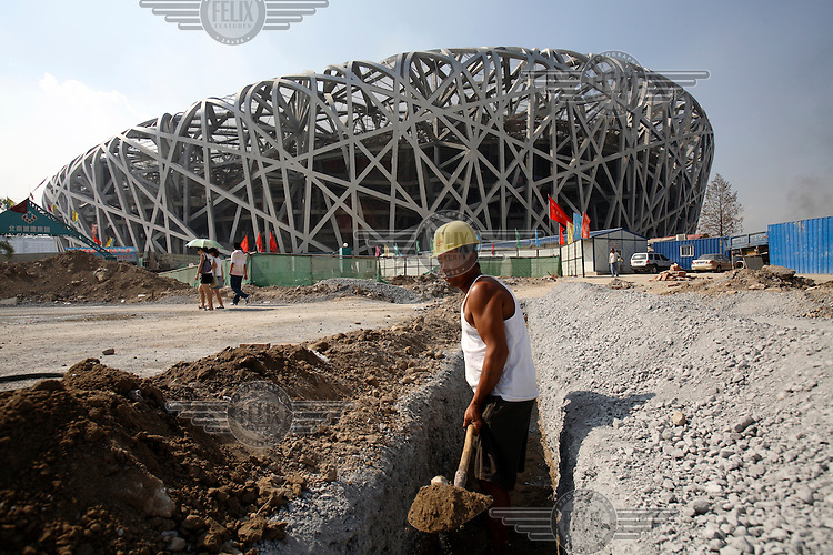 "A construction worker digs a ditch in front of the Beijing Olympic Games' National Stadium, ""The Bird's Nest""."