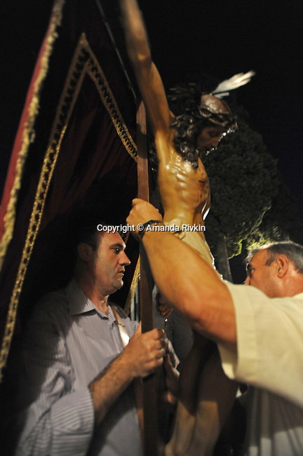 Men carry Jesus on the cross after arriving at the cavalry and cemetery following a procession during the municipal fiestas in Costur, Spain on August 16, 2009.
