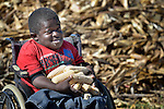 Peter Makura inspects corn on his farm in the village of Berejena, near Masvingo, Zimbabwe. The Jairos Jiri Association provided Makura with his wheelchair with support from CBM-US.