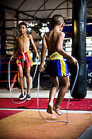 One Pi Chit 7 years old (right) and One Pi Chie 9 years old (left) are two brothers who live outskirts of Bangkok, in Nonthaburi. Their father drives a tuk tuk (small thai taxi) and he help to train them every time at gym. Their mother attends every training as well, helping them to roll up the bandaging they use to protect the hands, and hugs the training bag while they kick it. Parents encourage them to train heaviness and scream with passion  when they only play, but they play and smile while punch each other, meanwhile on the ring they transform themselves into tough fighters instead.