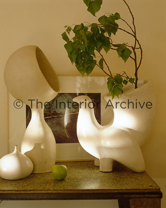 Ceramic vases in the shape of a dove and one resembling a stylised eskimo stand on a side table