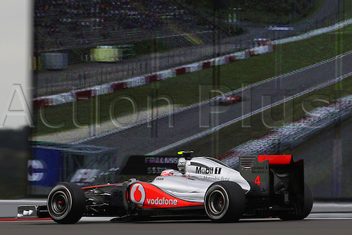 22 07 2011  FIA Formula One World Championship 2011 Grand Prix of Germany 04 Jenson Button GBR Vodafone McLaren Mercedes shows as he passes a large video screen showing another part of the track. motor racing Formula 1 Nuerburg Nuerburgring