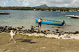 MAURITIUS, Trou D'eau Deuce, fisherman Rolau Dardenne (age 80) prepares his boat to go fishing off of the East coast of Mauritius, Indian Ocean, 4 Sisters Mountain in the distance