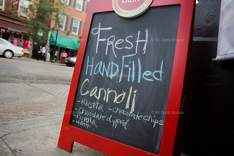 A sign advertises fresh handfilled cannoli on Hanover Street in the North End in Boston, Massachusetts, USA.