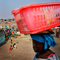 A woman hawking small items, kept in a plastic basket carried on her head, walks through the slum or musseque near Luanda's airport.