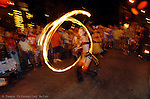 A fire twirler gathers a crowd in Key West during the annual Fantasy Fest.
