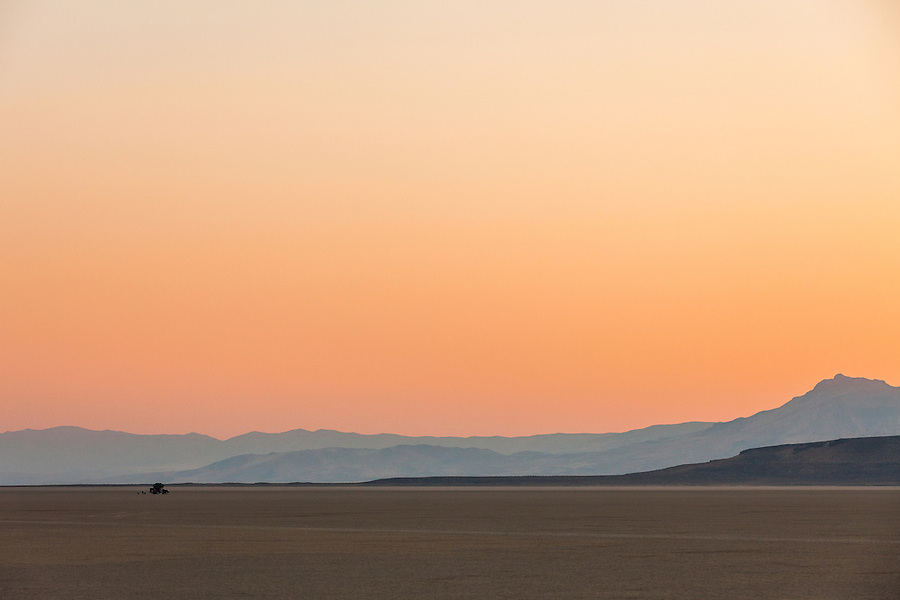An overlander experiences the serene soft orange and red light after sunset in the Alvord Desert in a remote part of Southeast Oregon while overland camping with a rooftop tent.