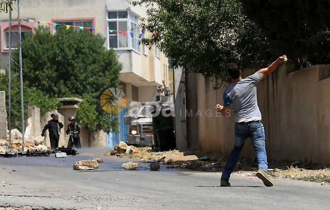 A Palestinian protester hurls stones towards Israeli security forces during clashes following a demonstration against the expropriation of Palestinian land by Israel, on May 20, 2016 in the village of Kfar Qaddum, near Nablus, in the occupied West Bank. Photo by Nedal Eshtayah