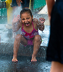 WATERBURY,  CT-071919JS13--  Leah Thompson, 4, gets hit with cold water from an open fire hydrant she and other kids play during a block party at Berkeley Heights on an oppressively hot day Saturday. The hydrant was opened by members of Waterbury Fire Department Engine 7 on Walnut Street. <br /> Jim Shannon Republican American