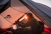 Hiker awakes at sunrise in tent on summit of Skierfe, Sarek National Park, Lapland, Sweden