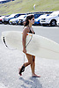 Woman heading to the surf at Bondi Beach in Sydney, Australia