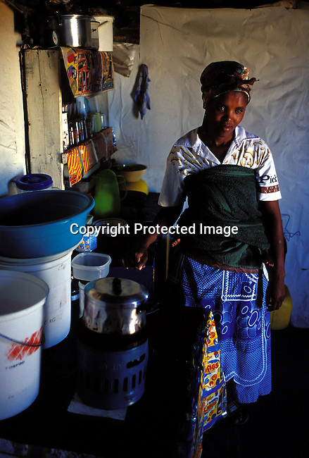 ditown00250 .Digital. Culture, Township A women cooking food on a gas primus in her kitchen on July 21, 2001 in Site B Khayelitsha, a township about 35 kilometers outside Cape Town, South Africa. Pots, buckets..©Per-Anders Pettersson/ iAfrika Photos.