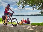 Mrągowo 2019-08-11. Rowerzysta na promenadzie nad jeziorem Czos. Letni wypoczynek na plaży miejskiej w Mrągowie mieście w województwie warmińsko-mazurskim, popularnym ośrodku wypoczynkowym na Mazurach.
