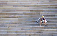 02 NOV 2003 - ATHENS, GREECE - A competitor recovers on the steps of the Kallimarmaro Stadium after finishing the 21st Athens Classic Marathon. (PHOTO (C) NIGEL FARROW)