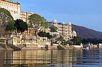 Late afternoon light illuminates the CITY PALACE of UDAIPUR and LAKE PICHOLA- RAJASTHAN, INDIA