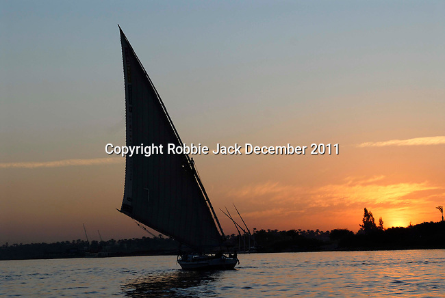 A felucca on the River Nile at Luxor at sunset.The town of Luxor occupies the Eastern part of a great city of antiquity which the ancient Egytians called Waset and the Greeks named Thebes.