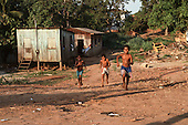 Acre State, Brazil. Three smiling caboclo boys running through a very poor settlement in the Amazon with wooden shacks.