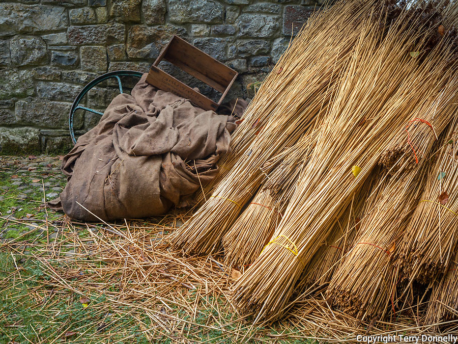 Clare County, Ireland:<br /> Burlap and bundles of thatch stacked against a stone wall