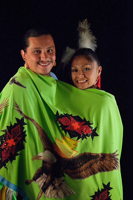 Native American boyfriend and girlfriend share traditional green shawl on black background. Boyfriend Jeremy Ball (Shoshone-Bannock) with girlfriend's shawl