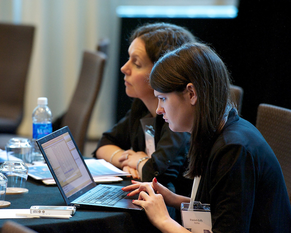 Candid photo of conference attendee working on her laptop.