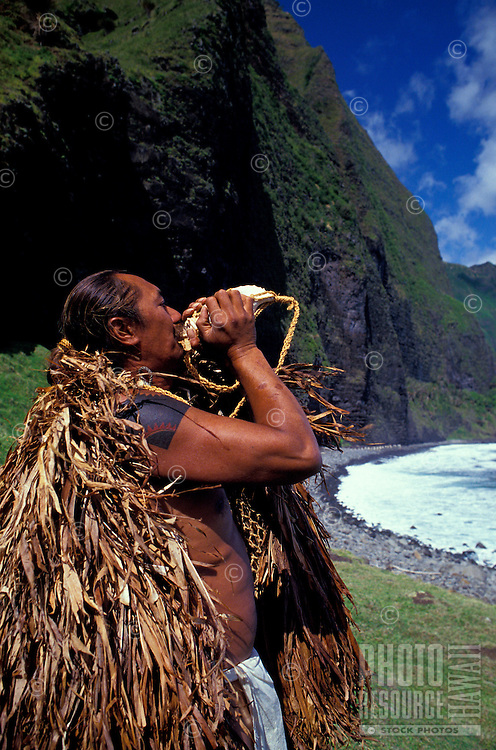 """EDITORIAL ONLY. Man in traditional """"""""rain cape"""""""" blowing conch shell. Waikolu Valley, Molokai"""