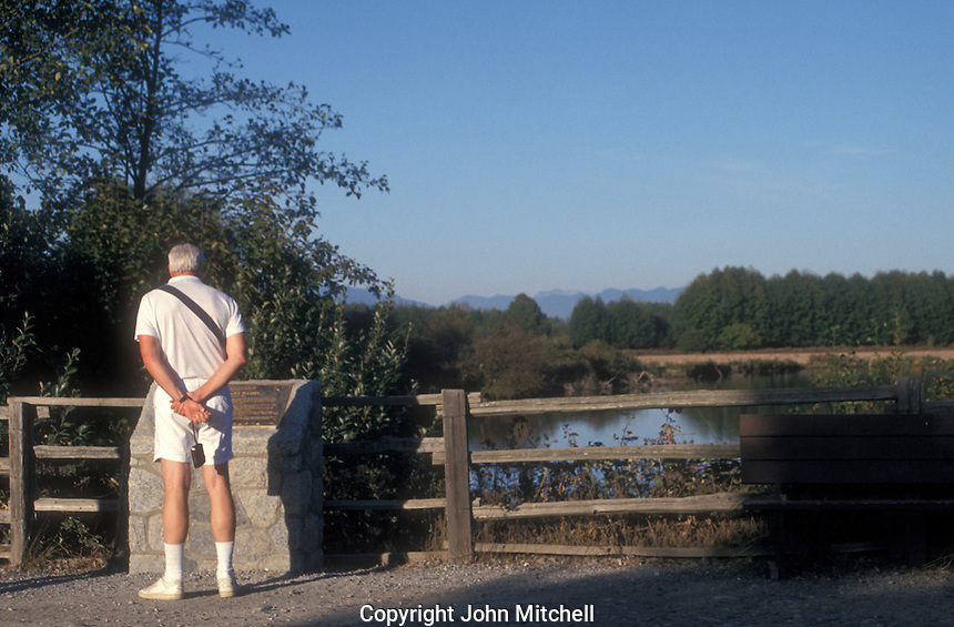 Man reading an interpretive sign at the George C. Reifel Migratory Bird Sanctuary in Delta, BC, Canada.